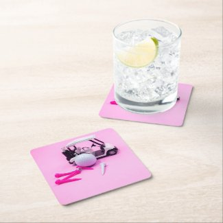 Golf ball with pink cart and white tee on pink square paper coaster