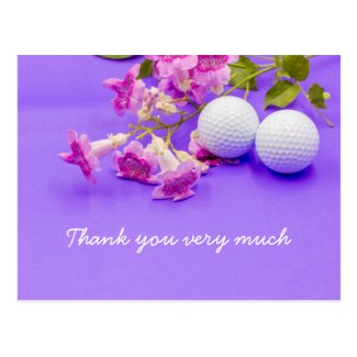 Golf ball with pink flowers on purple background postcard
