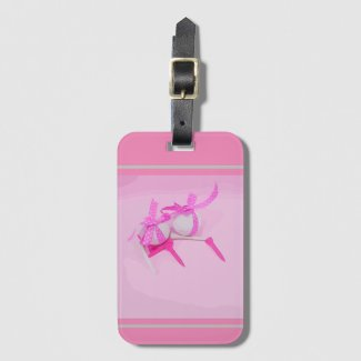 Golf ball with pink ribbon and tee on pink luggage tag