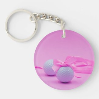 Golf ball with pink ribbon on pink background keychain