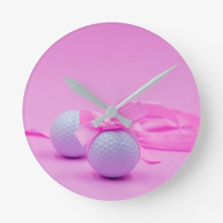 Golf ball with pink ribbon on pink background round clock