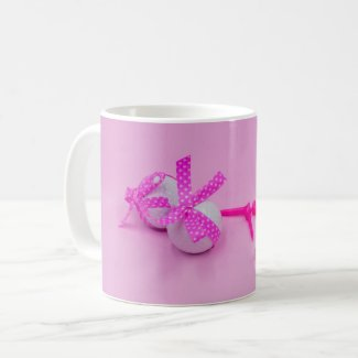 Golf ball with pink ribbon on pink coffee mug