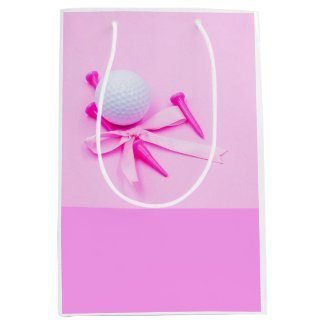 Golf ball with pink tee on pink background medium gift bag