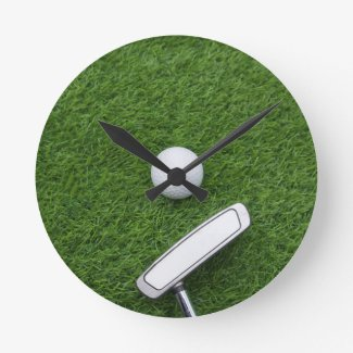 Golf ball with putter are on green grass round clock