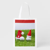 Golf ball with Santa Hat are on green grass Grocery Bag