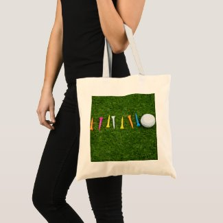 Golf ball with tees on green grass golf tote bag