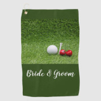Golf ball with two cherries on green golf towel