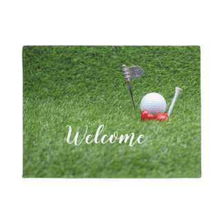 Golf ball with two red hearts are on green grass doormat
