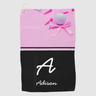 Golf ball with white tee are on pink background golf towel