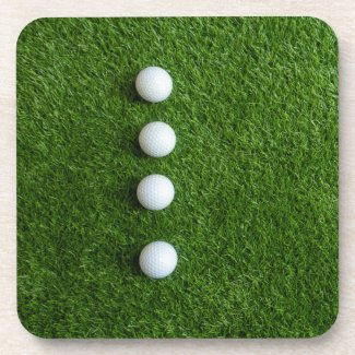 Golf balls are on green grass beverage coaster