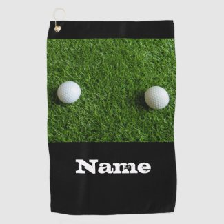 Golf balls are on green grass for golfer putting golf towel