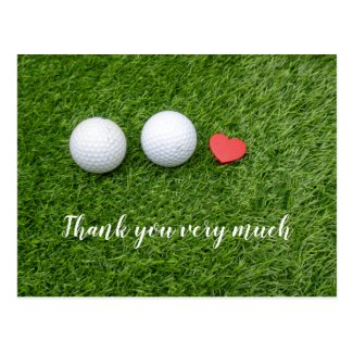 Golf balls are on green grass with love postcard
