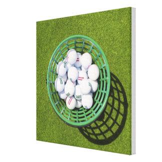Golf balls in a basket sitting on short green canvas prints