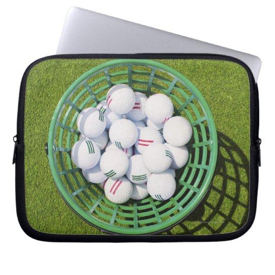 Golf balls in a basket sitting on short green laptop sleeve