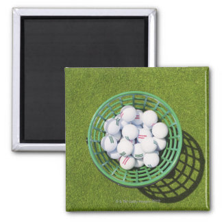 Golf balls in a basket sitting on short green magnet