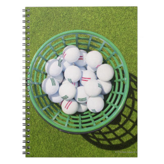 Golf balls in a basket sitting on short green note book