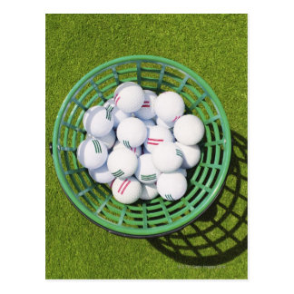 Golf balls in a basket sitting on short green postcard
