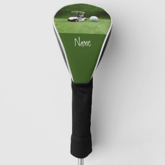 Golf cart with golf ball are on green grass golf head cover