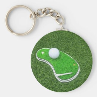 Golf course with tee on green grass background keychain