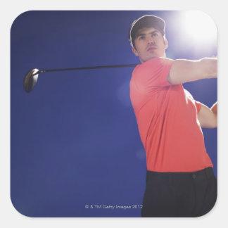 Golf player swinging club square sticker