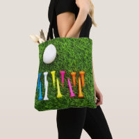 Golf tees are on green grass. tote bag
