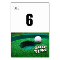 Golf time with golf ball next to ball on grass table number