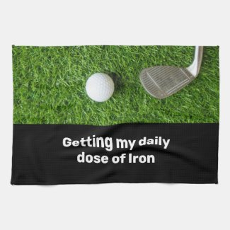 Golfer getting dose of iron and golf ball on green kitchen towel