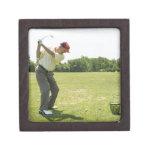 Golfista mayor que golpea bolas de la práctica en  cajas de recuerdo de calidad