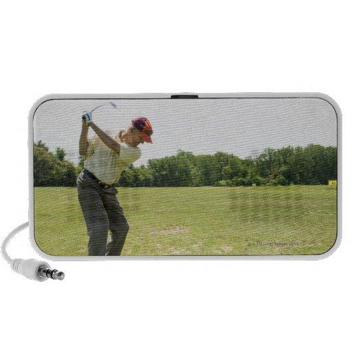 Golfista mayor que golpea bolas de la práctica en iPod altavoces