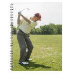 Golfista mayor que golpea bolas de la práctica en libro de apuntes con espiral