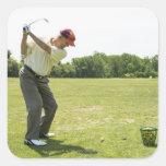 Golfista mayor que golpea bolas de la práctica en pegatina cuadrada