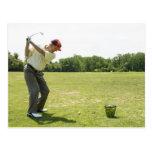 Golfista mayor que golpea bolas de la práctica en postales