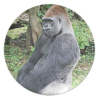 Gorila de la tierra baja en actitud que se sienta platos para fiestas