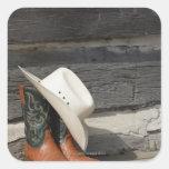 Gorra de vaquero en botas de vaquero fuera de una calcomanías cuadradass