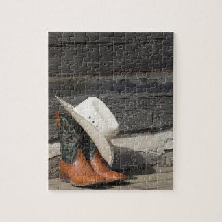 Gorra de vaquero en botas de vaquero fuera de una rompecabezas con fotos