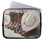 Gorra de vaquero en la fila de las botas de mangas portátiles