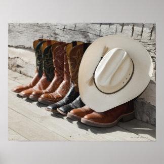 Gorra de vaquero en la fila de las botas de póster