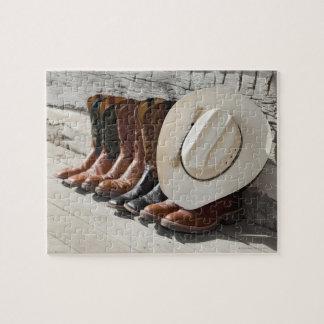 Gorra de vaquero en la fila de las botas de rompecabeza con fotos