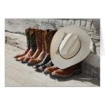 Gorra de vaquero en la fila de las botas de tarjeta de felicitación