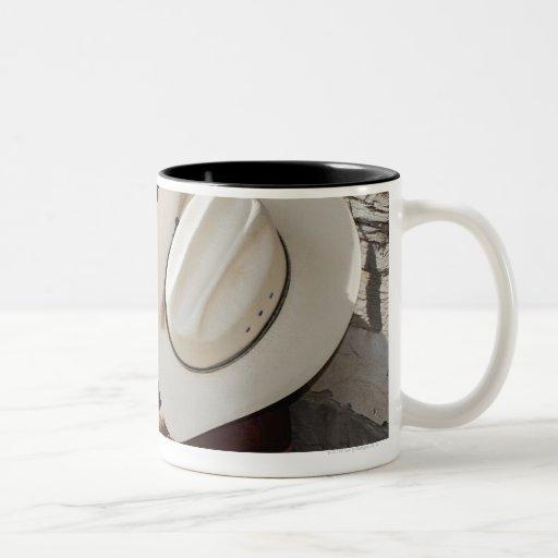 Gorra de vaquero en la fila de las botas de taza de café de dos colores