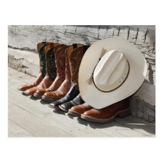 Gorra de vaquero en la fila de las botas de vaquer tarjeta postal