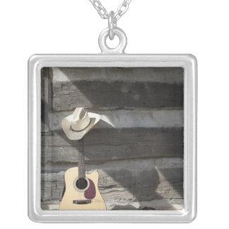 Gorra de vaquero en la guitarra que se inclina en colgante cuadrado
