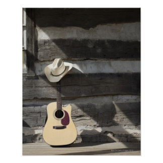 Gorra de vaquero en la guitarra que se inclina en póster
