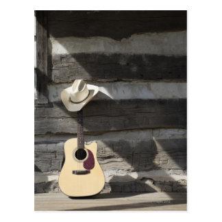 Gorra de vaquero en la guitarra que se inclina en postal