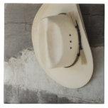 Gorra de vaquero que cuelga en la pared de la caba azulejo cuadrado grande