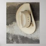 Gorra de vaquero que cuelga en la pared de la caba póster