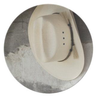Gorra de vaquero que cuelga en la pared de la platos
