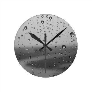 Gotas de agua en el fondo de plata reloj redondo mediano