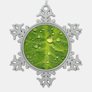 Gotas de agua en la hoja del taro adorno de peltre en forma de copo de nieve