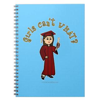 Graduado ligero de la mujer en vestido rojo libro de apuntes con espiral